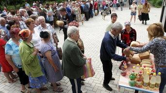 Местные жители стоят в очереди во время раздачи бесплатного хлеба в Донецке, Украина