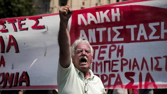Протестующий кричит лозунги во время митинга в Афинах, Греция