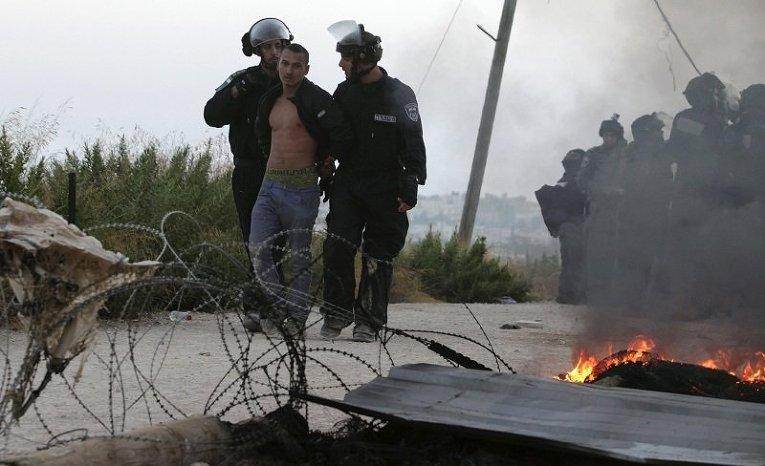 Израильская полиция задерживает еврейского поселенца, который протестовал против сноса зданий по приказу высшего суда Израиля, на Западном берегу еврейского поселения Бейт-Эль