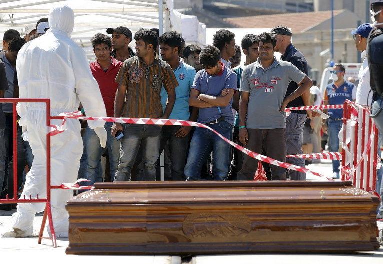 Мигранты стоят перед гробами после высадки с ирландского корабля ВМФ LE Niamh в сицилийском порту Мессина