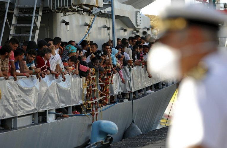 Мигранты ждут высадки с ирландского корабля ВМС LE Niamh в сицилийском порту Мессина