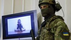 Офицер СБУ стоит рядом с монитором, на котором показан человек, являющийся, по данным СБУ, майором российской армии. Он был задержан украинскими спецслужбами на днях