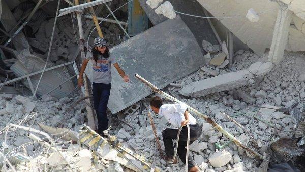 На месте падения военного самолета на жилые дома в городе Эриха неподалеку от Идлиба на северо-западе Сирии