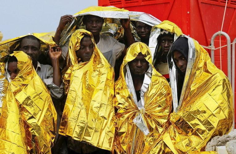 Мигранты ждут, чтобы сойти с корабля береговой охраны в сицилийском порту Мессина, Италия