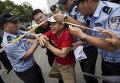 Полиция пытается остановить мужчину, чей родственник был на борту рейса Malaysia Airlines MH370, который пытается попасть в Посольство Малайзии в Пекине