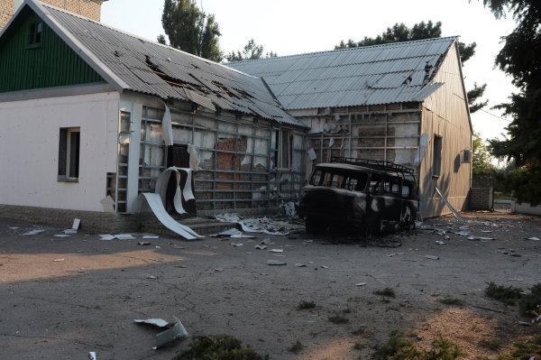 Разрушенный в результате обстрела дом и сгоревшая автомашина на одной из улиц Иловайска