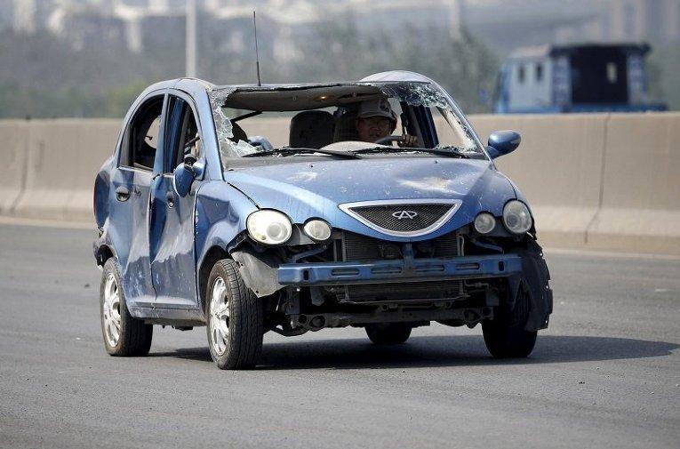 Водитель едет в машине, поврежденной в результате мощного взрыва в китайском городе Тяньцзине