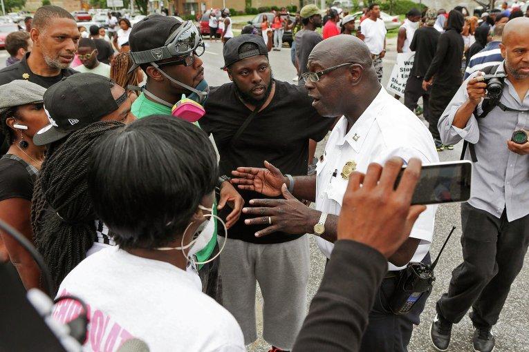 Чернокожий полицейский в Сент-Луисе успокаивает участников митинга