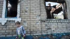 Ребенок у разрушенного в результате обстрела дома в поселке Александровка Донецкой области. Архивное фото