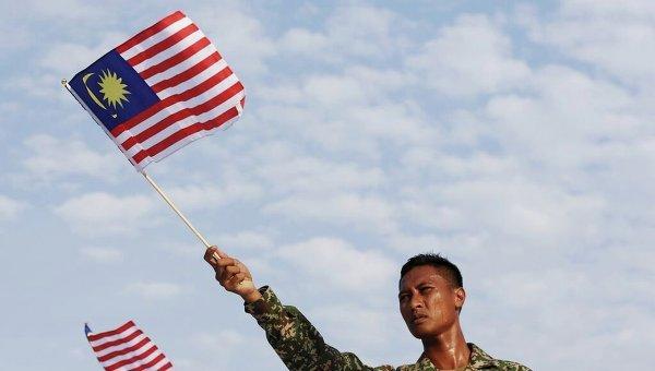 Военный держит флаг Малайзии