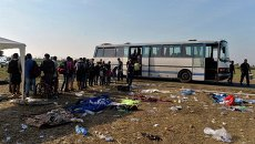 Мигранты выстраиваются на борт автобуса для поездки в транзитный центр для мигрантов на границе между Венгрией и Сербией. Архивное фото