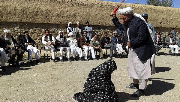 Афганский судья бьет женщину кнутом перед толпой в провинции Гор, в Афганистане, за супружескую измену