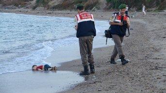 Турецкие полицейские рядом с телом маленького сирийского мигранта, который утонул вместе с другими мигрантами, когда их лодка перевернулась.