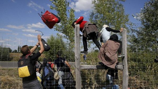 Мигранты перепрыгивают через забор, покидая пункт сбора в деревне Венгрии