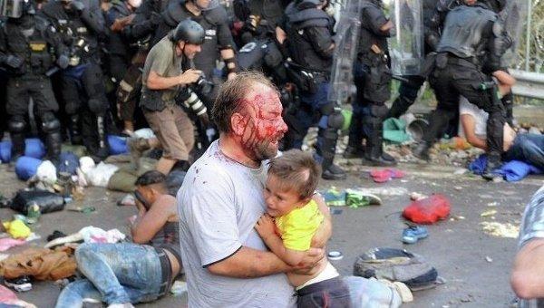 Травмированный мигрант несет ребенка во время столкновений с полицией Венгрии