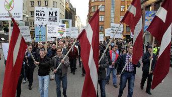 Шествие против приема беженцев в Риге под национальными флагами Латвии