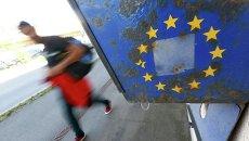 Мигранты и флаг ЕС. Архивное фото