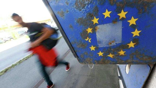Мигранты проходят мимо флага ЕС