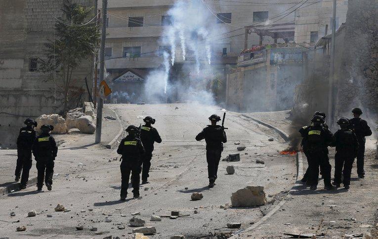 Израильские полицейские выпускают слезоточивый газ по протестующим из Палестины.