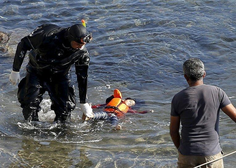 Двое детей и женщина погибли, еще четыре человека пропали без вести около греческого острова Лесбос в четверг после того, как их лодка столкнулась с греческим спасательным судном. На фото - спасатели обнаружили тело утонувшего ребенка 18+