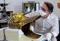 Немецкий реставратор Кристиан Экмана рассматривает бороду золотой маски знаменитого египетского фараона Тутанхамона перед началом реставрационных работ