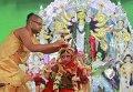 В Индии священник наряжает пятилетнюю девочку для празднования Дурга-пуджа.
