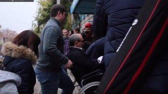 Мэра Харькова Геннадия Кернес заносят в инвалидном кресле в избирательный участок
