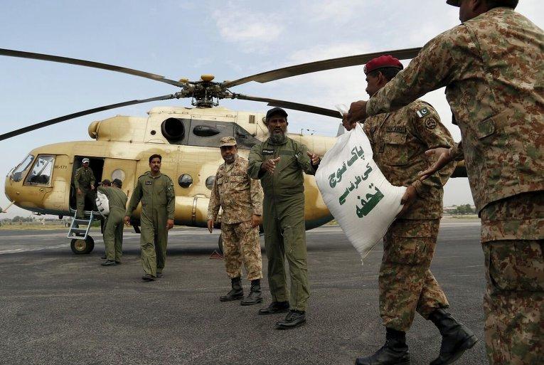 Солдаты загружают мешки продовольственной помощи на вертолет для пострадавших в Пешаваре, Пакистан