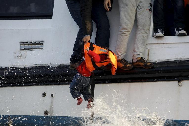 Греческая рыбацкая лодка эвакуирует людей из наполовину затонувшего катамарана, на борту которого было около 150 беженцев, большинство из них - сирийцы