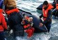 Беженцы в турецкой провинции Измир собираются на пляже перед отплытием на греческий остров Хиос